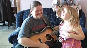 "Dad Plays Back Up For 5-Year-Old Singing ""Coat Of Many Colors"""