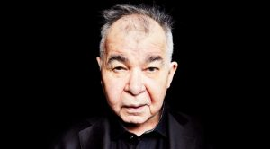 "John Prine's Wife Says He Is Still ""Very Ill,"" Has Been In ICU For Over A Week"